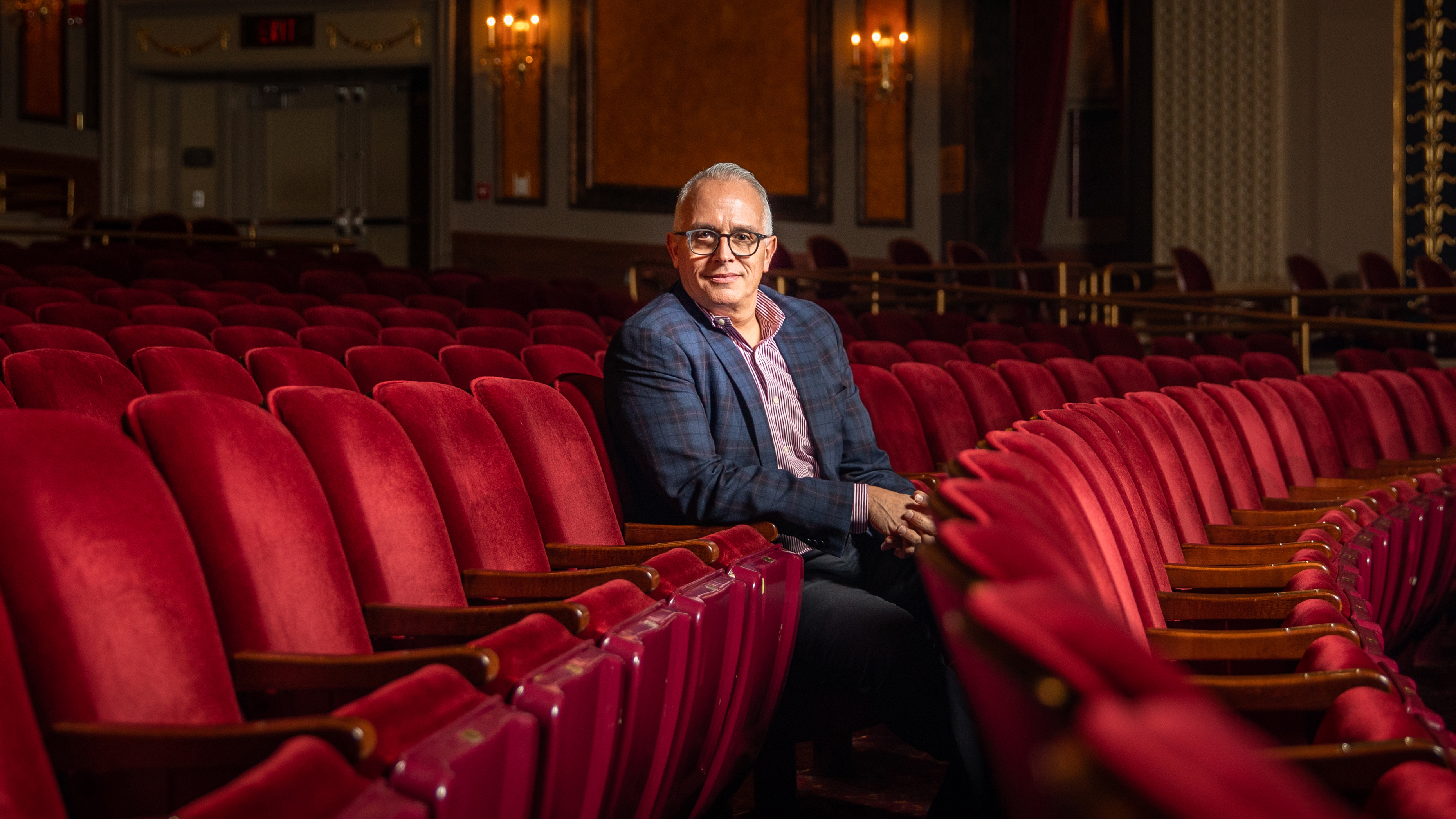 Frank Tavera sitting in the red seats at The Palace Theater is Waterbury CT