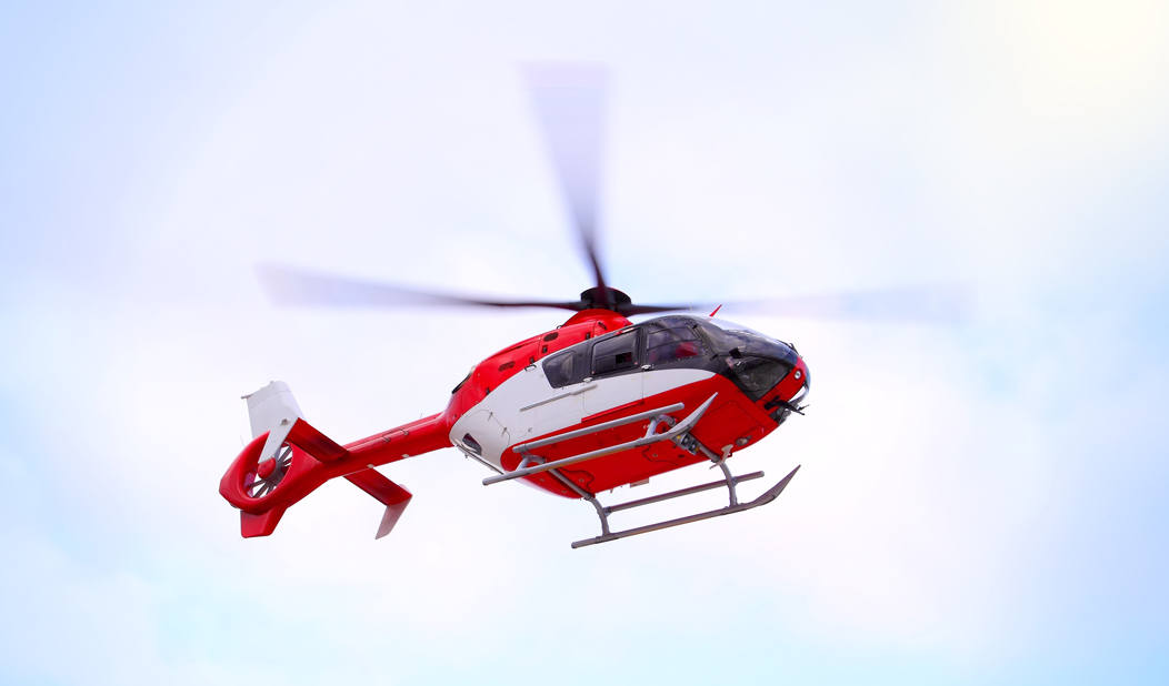 Red and white emergency services helicopter flying in the air