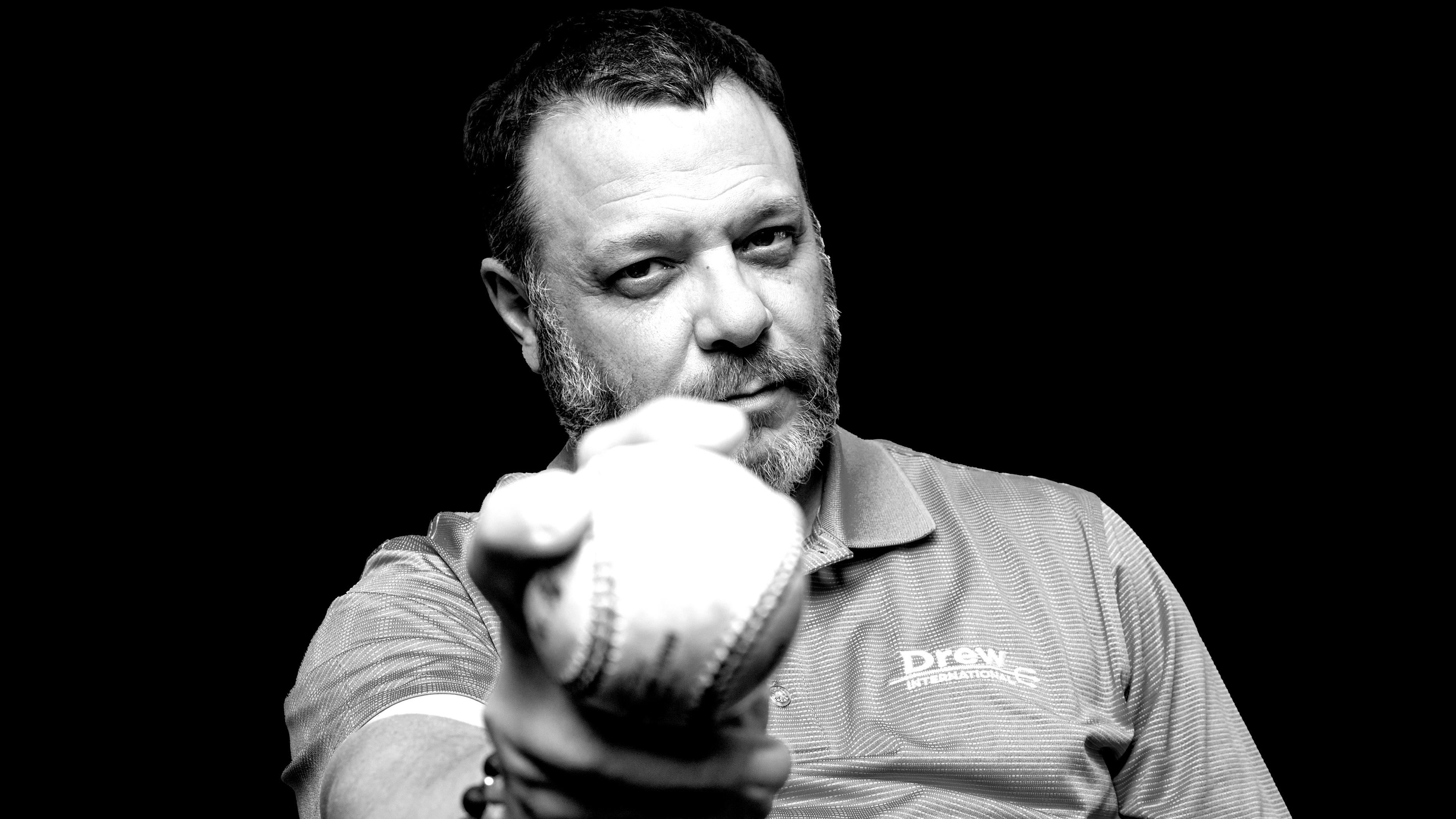 Black and white photo of Frank Monteiro of Waterbury CT holding a baseball, wearing a Drew International shirt