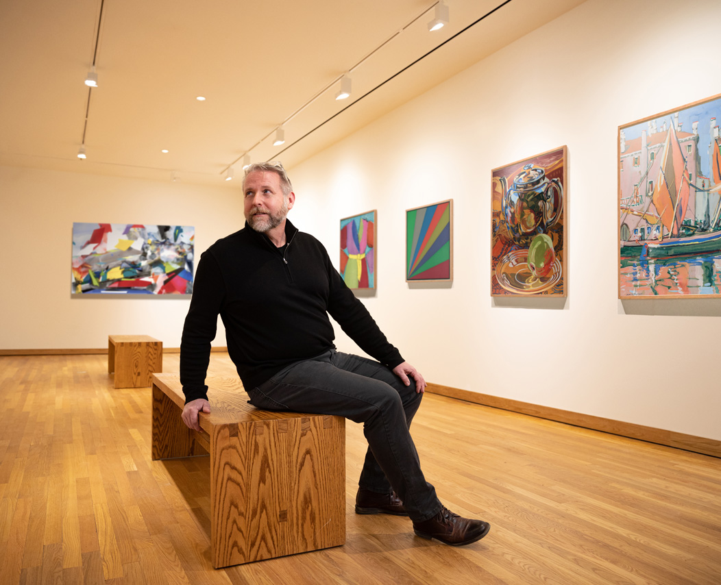 Bob Burns sitting on a viewing bench in one of the art galleries at the Mattatuck Museum