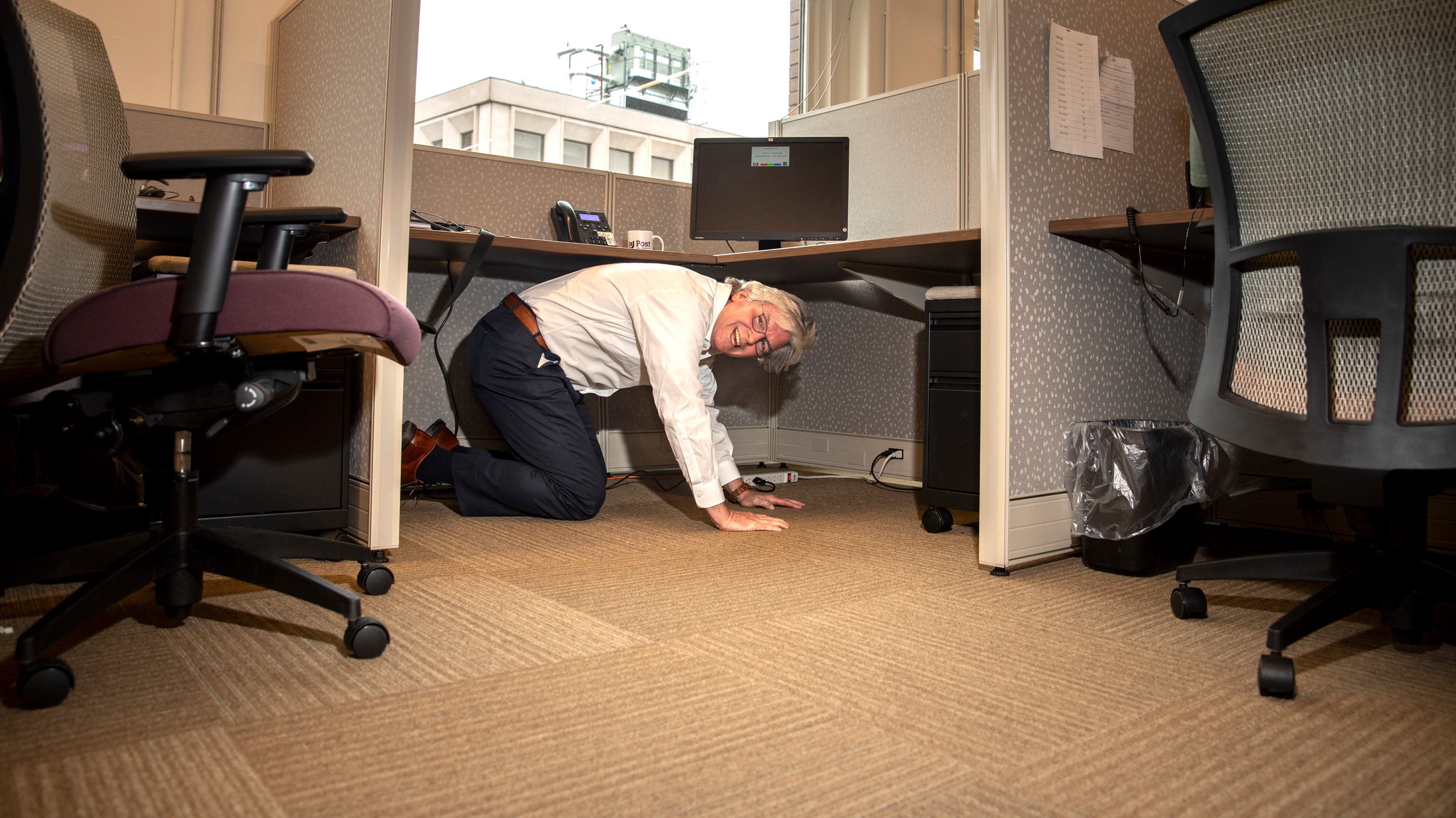John Hopkins on hands and knees underneath an office desk and smiling