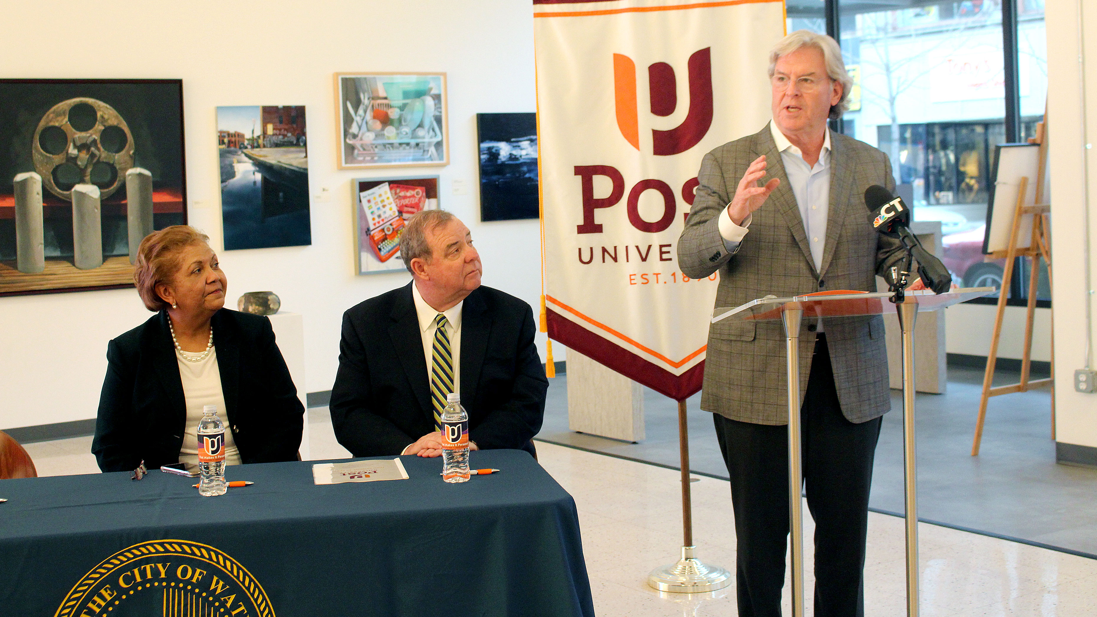John Hopkins giving a speech at Post University in Waterbury CT as Dr. Verna Ruffin and Major Neil O'Leary look on