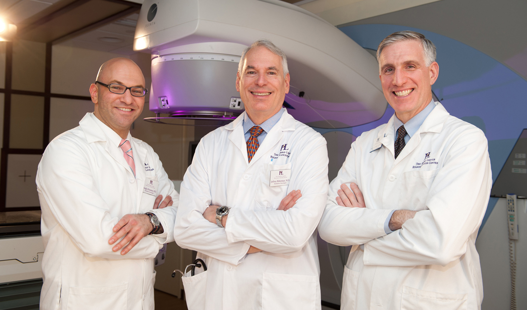 Three male doctors in white coats smiling and standing with arms crossed in the Harold Leever Regional Cancer Center in Waterbury