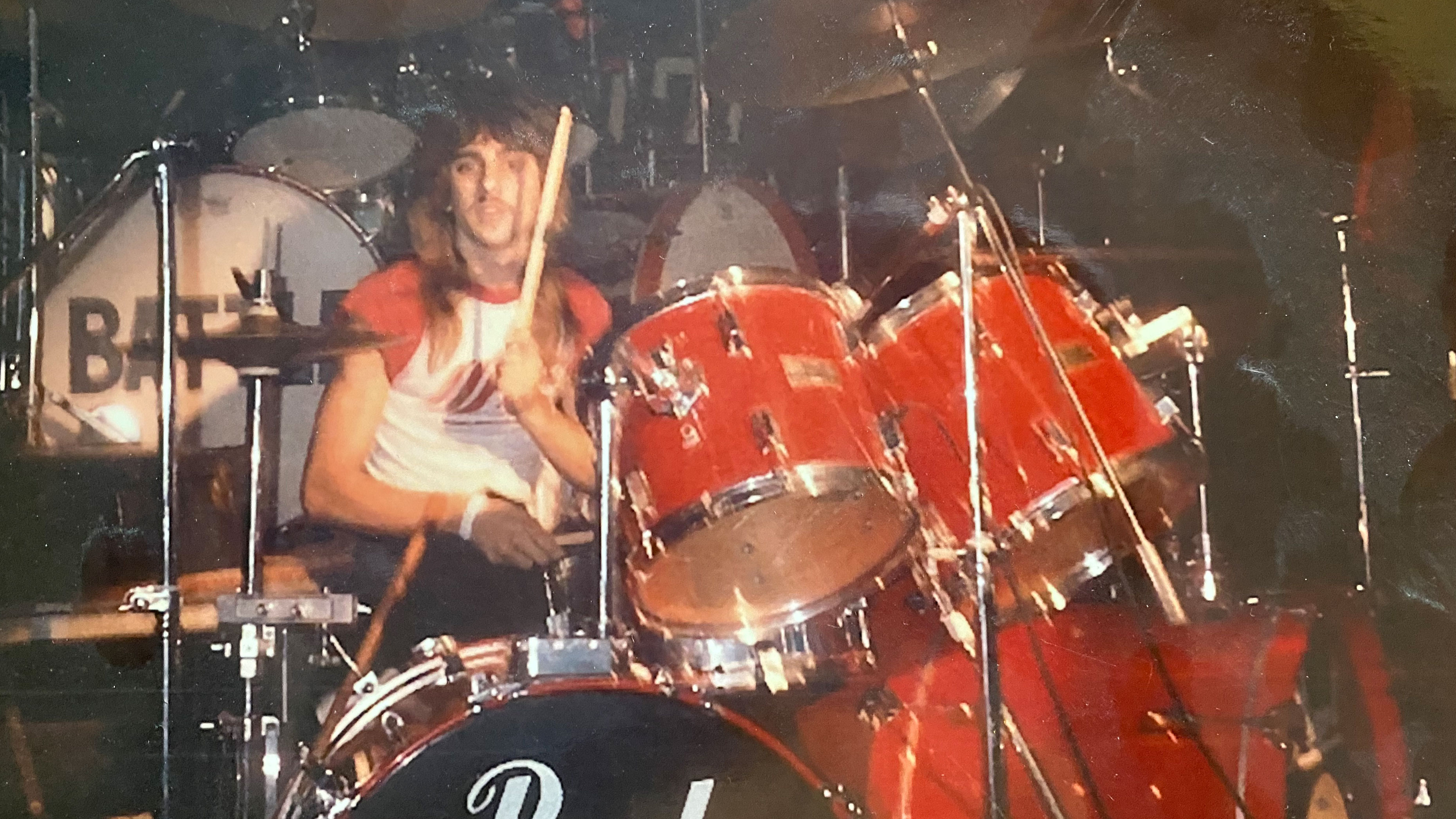 Photo of young Joe Gramando playing a red drumset