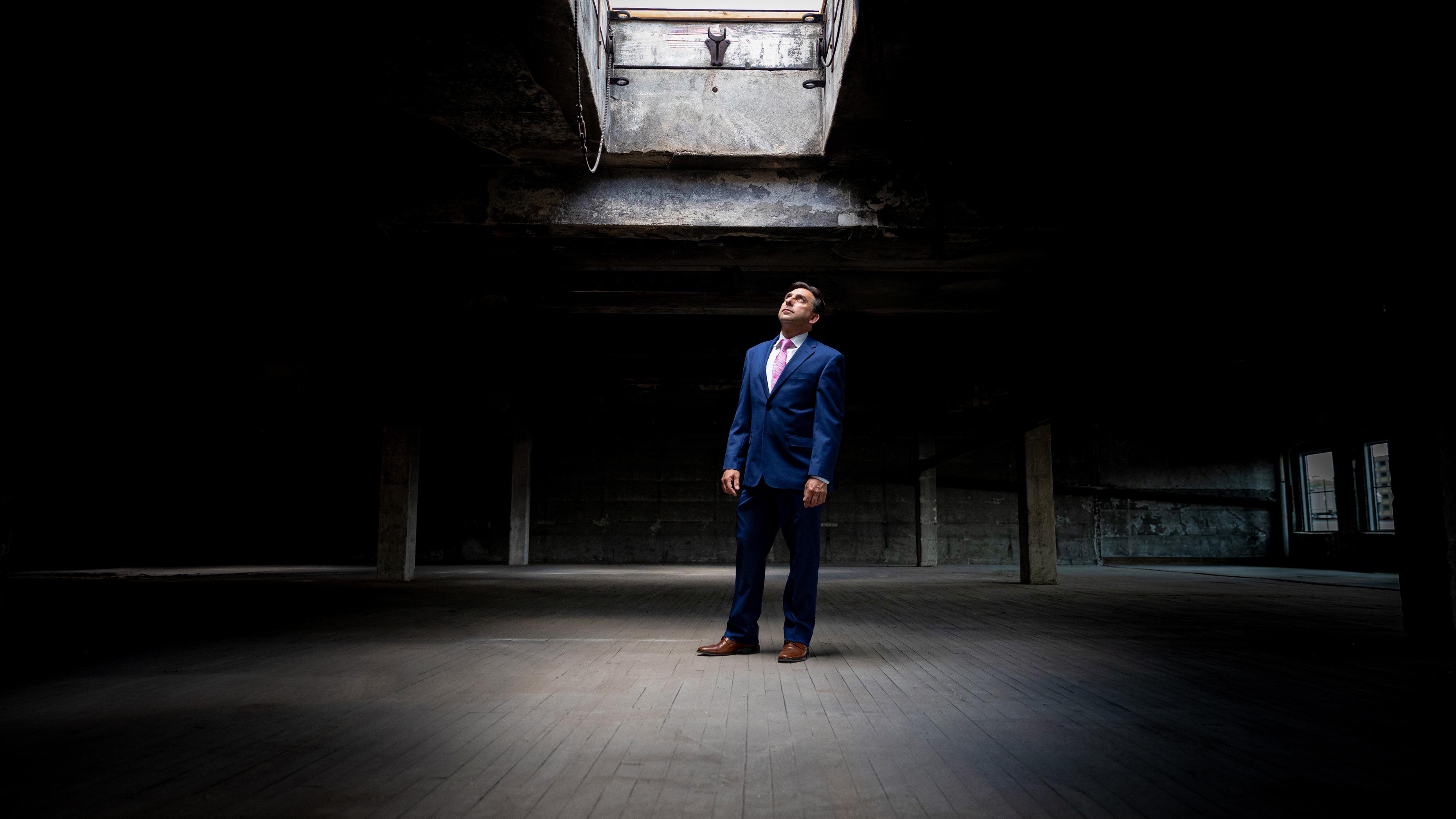 Joe Gramando of Waterbury CT standing under an open skylight in a dark building