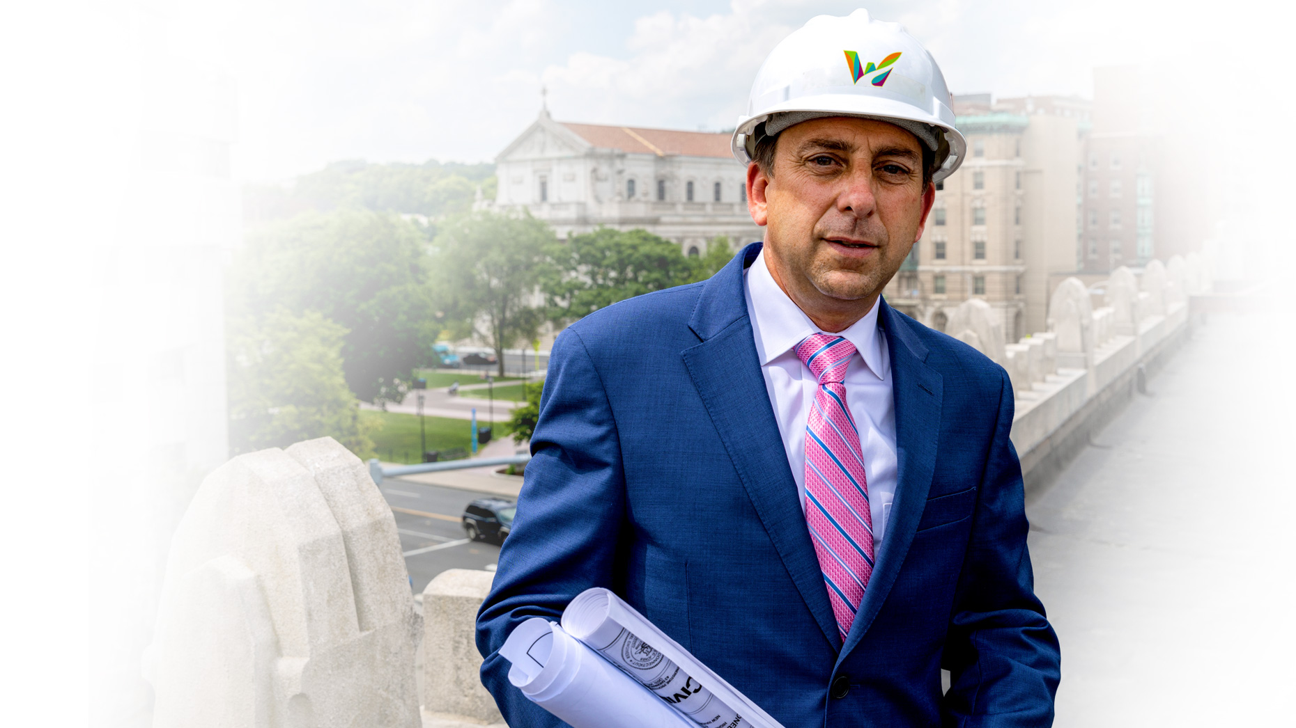 Joe Gramando wearing a Waterbury hard hat and holding blueprints, standing by the Waterbury Green