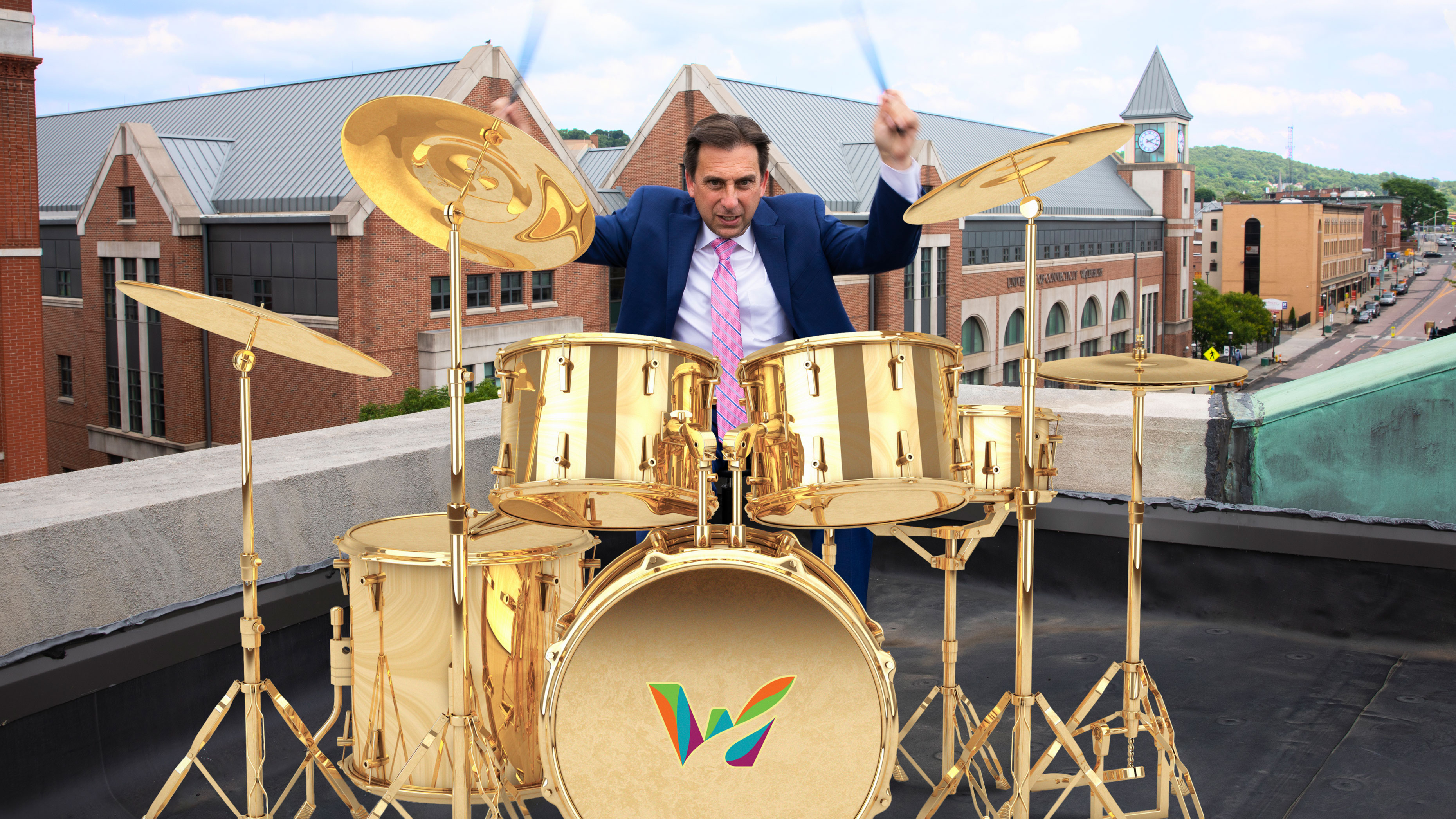 Joe Gramando playing drums on a rooftop in Waterbury CT, drumset showing the Waterbury logo