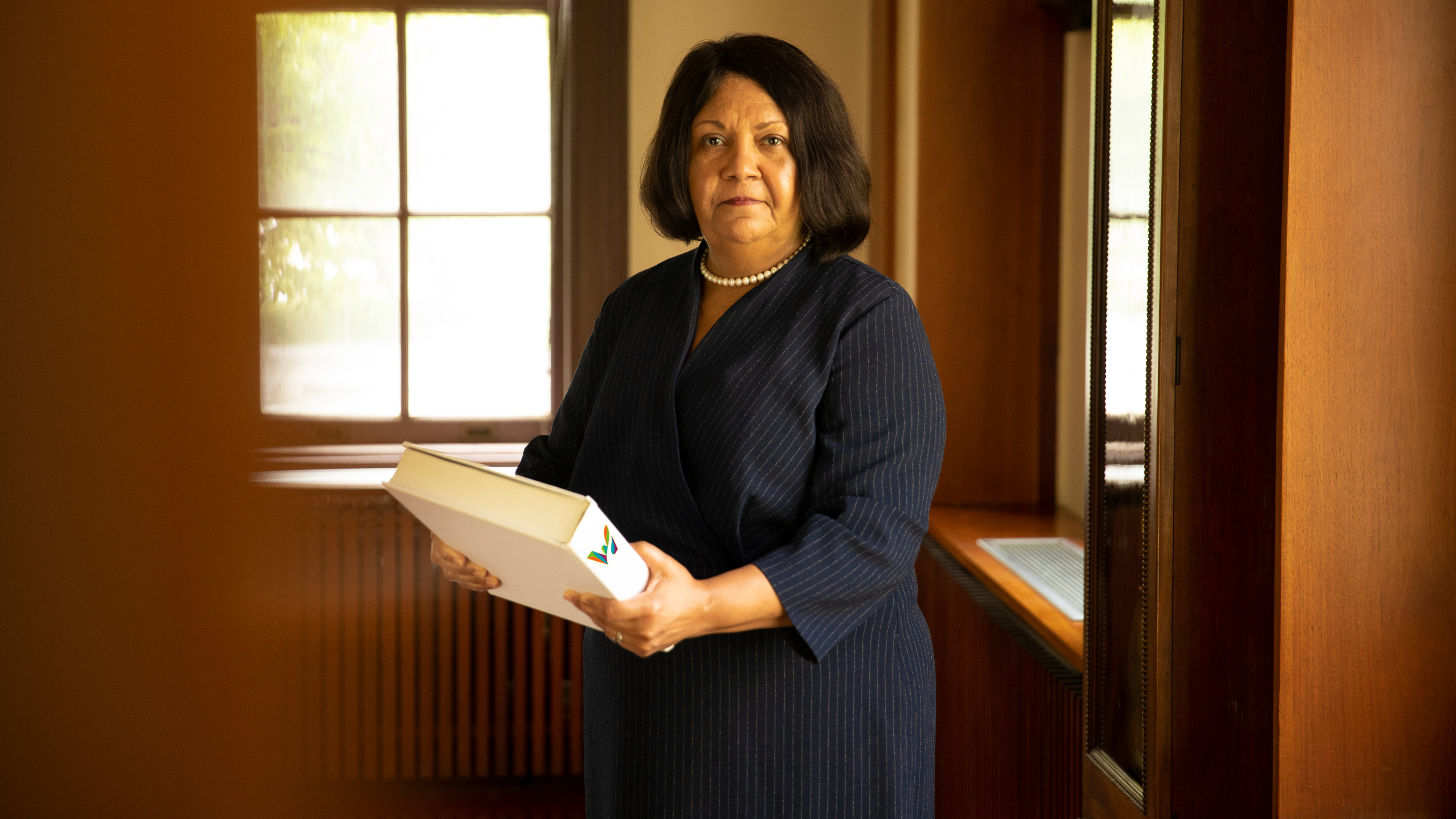 Superintendent of Waterbury Public Schools Verna Ruffin holding a large book with the Waterbury logo