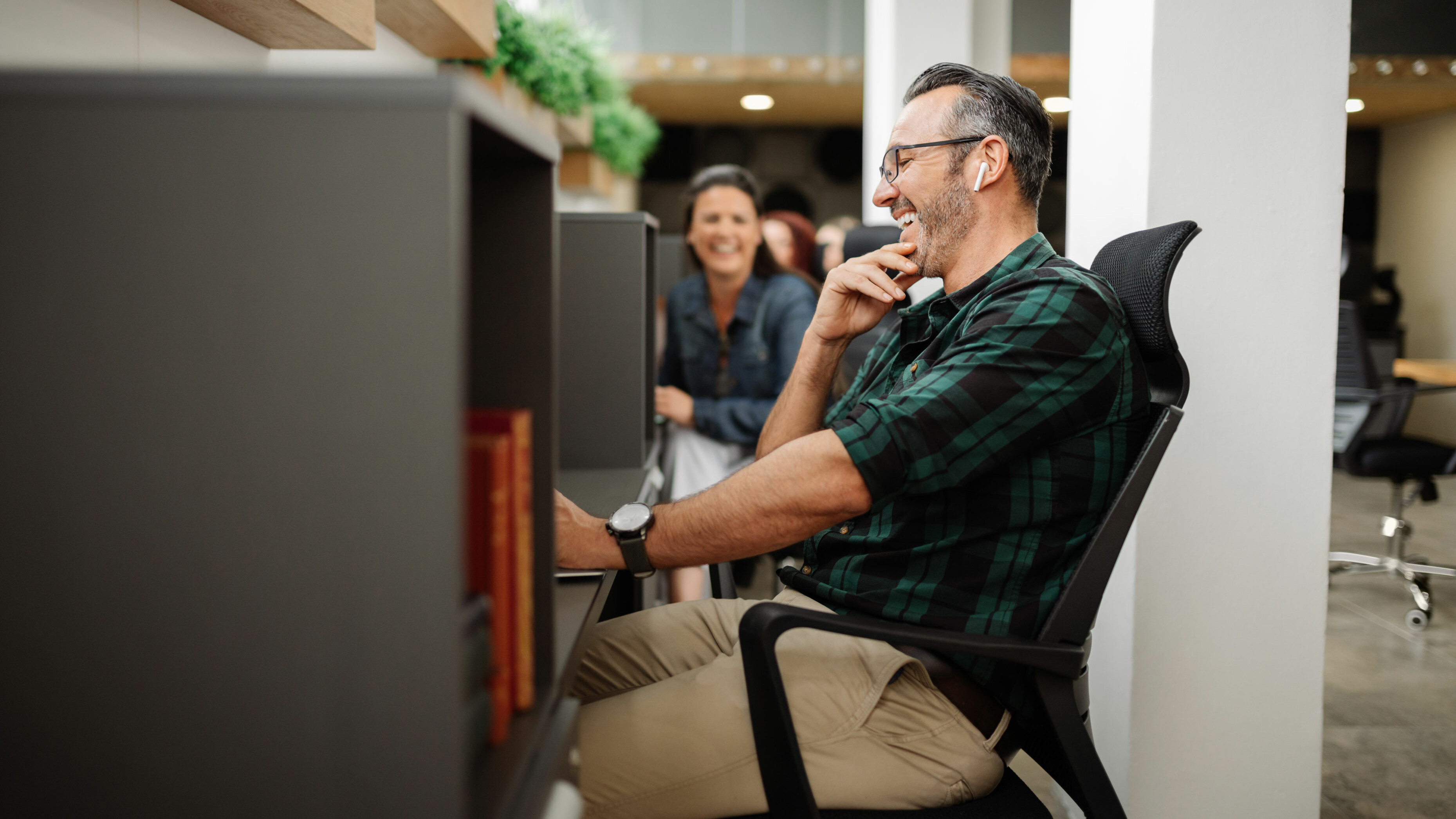 Man sitting at a cubical desk smiling and laughing as coworker next to him smiles
