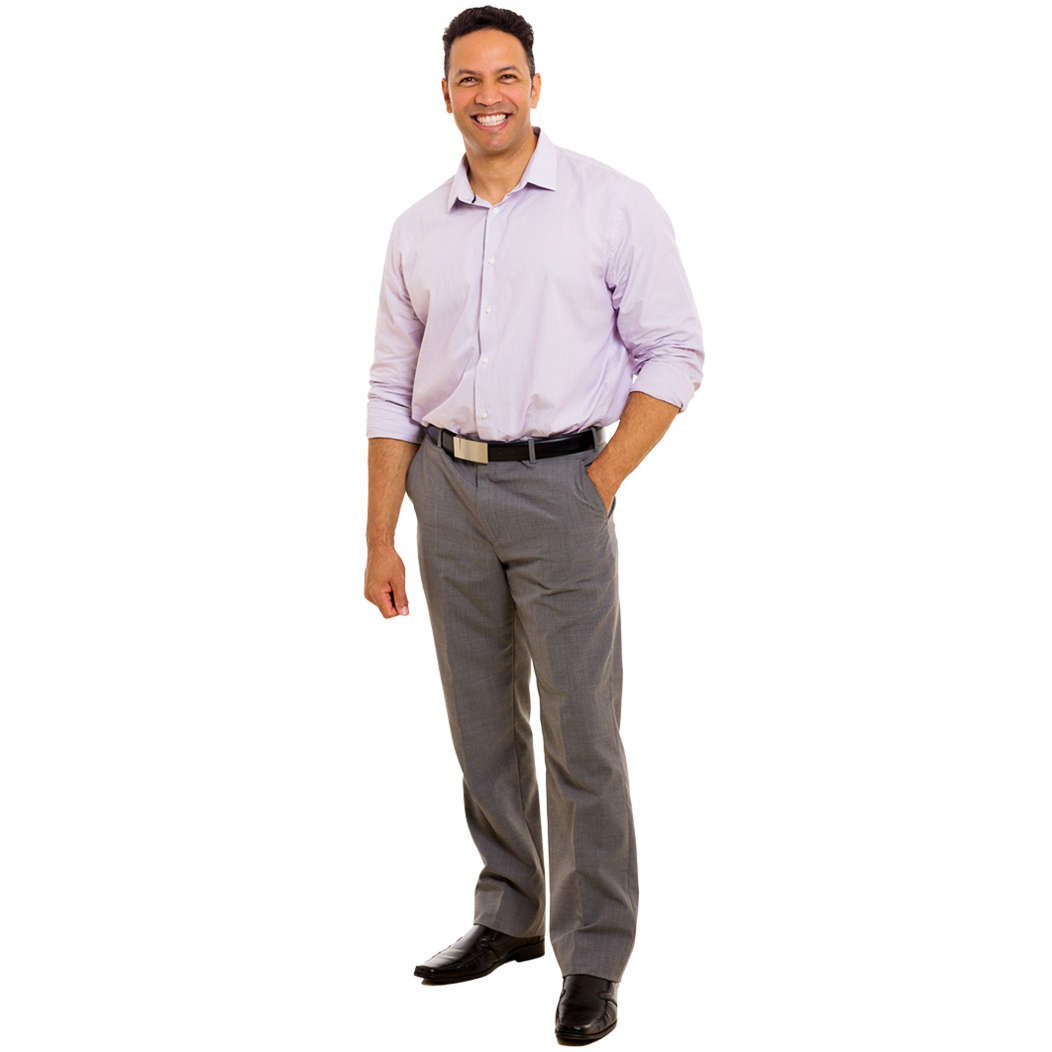 A male professional standing and smiling with one hand placed in his pocket