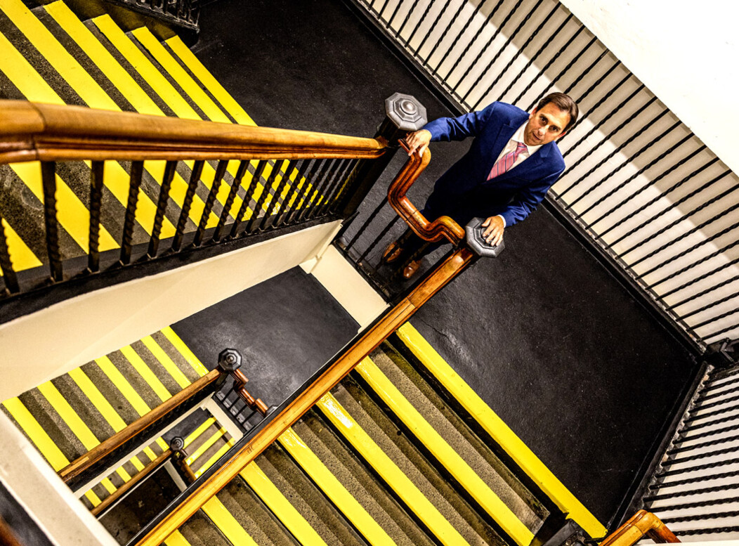 Joe Gramando standing on the stairs at the Howland Hughes Building in Waterbury CT, looking up