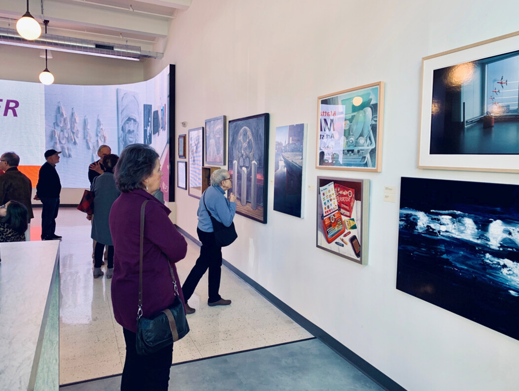 Patrons viewing framed artwork on the walls at Post University art gallery exhibit in Waterbury CT