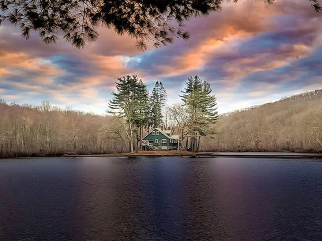 A house and trees on a small island at Tobys Pond in Beacon Falls CT