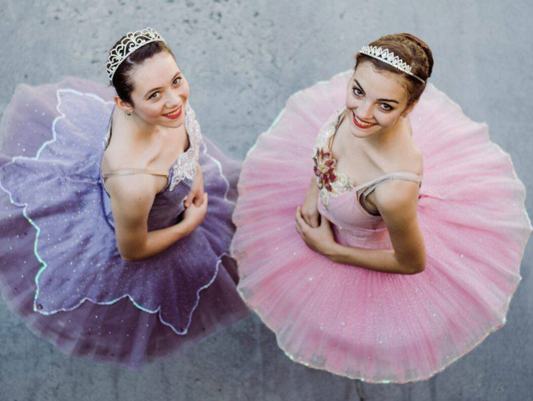 Two female ballet dancers in pink and purple tutus looking up