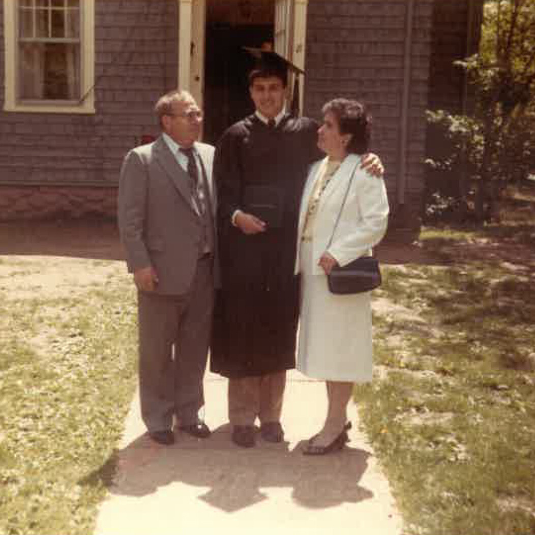 Older photo of Frank Tavera of Waterbury CT standing with parents after graduating from UConn graduation
