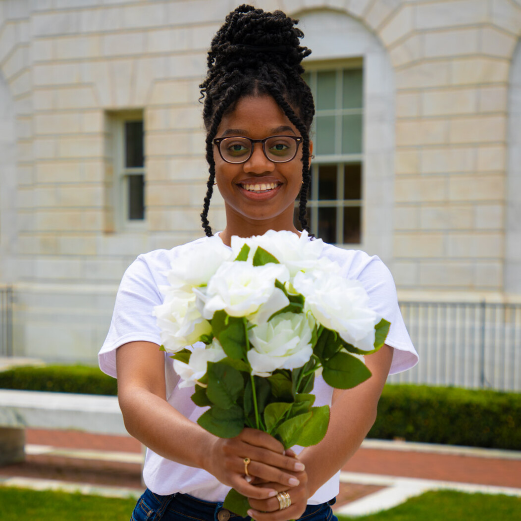 Waterbury woman smiling and holding a bunch of white flowers in front of her