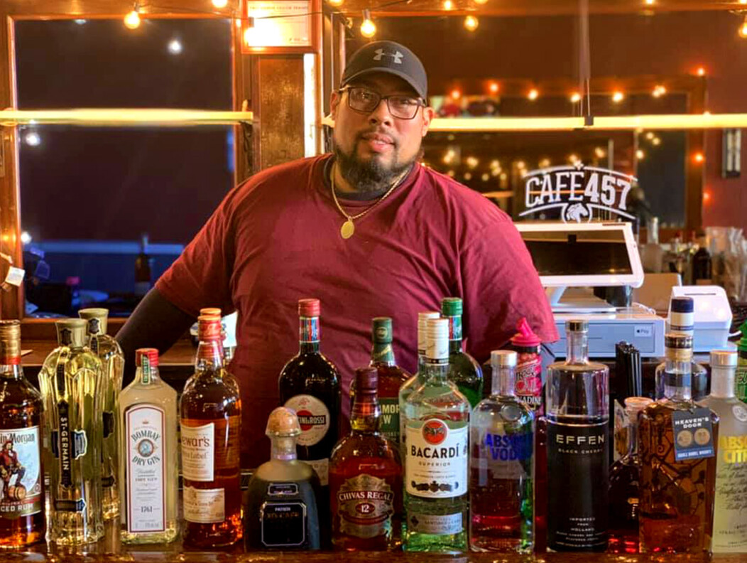 Man standing behind a bar filled with various liquor bottles at Cafe 457 in Waterbury CT