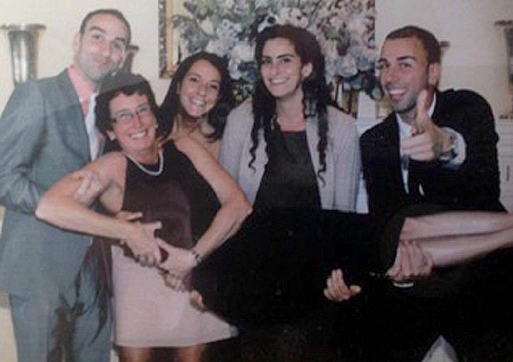 Cathy Awwad being lifted up by her four children for a family picture