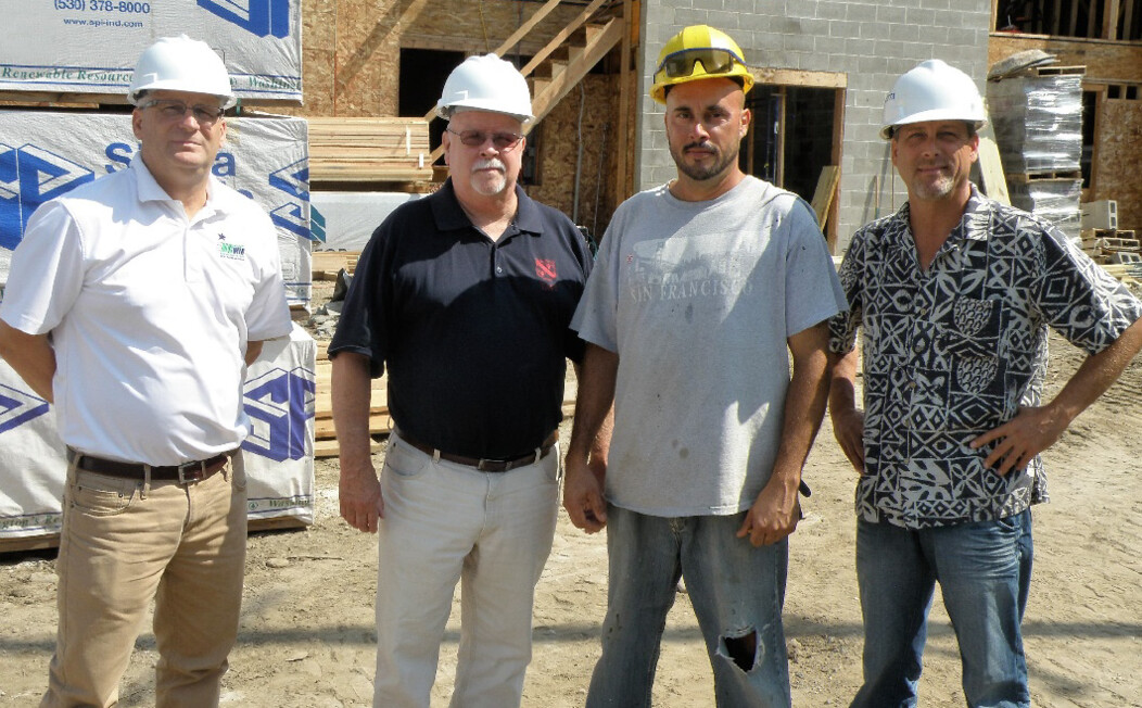 Four Waterbury CT men standing at a construction site and wearing white and yellow hard hats
